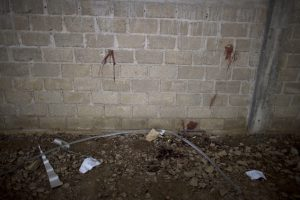 In this Thursday, July 3, 2014 photo, bullet holes and blood stains cover a wall above papers marking where bodies were found in an unfinished warehouse that was the site of a shootout between Mexican soldiers and alleged criminals on the outskirts of the village of San Pedro Limon, in Mexico state, Mexico. Bullet marks and blood spatters on the walls inside a grain storage warehouse deep in the mountains of southern Mexico tell a grim story of death involving soldiers and alleged criminals. It may not be the same story officials tell, however. Mexico's military says one soldier was wounded, and all 22 suspects were killed. (AP Photo/Rebecca Blackwell)